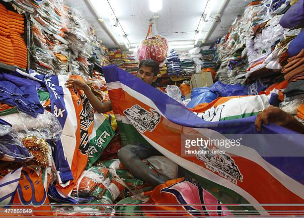 A shopkeeper displaying flags and banner of various political parties prepared for upcoming general elections at Lalbaug on March 11 2014 in Mumbai...