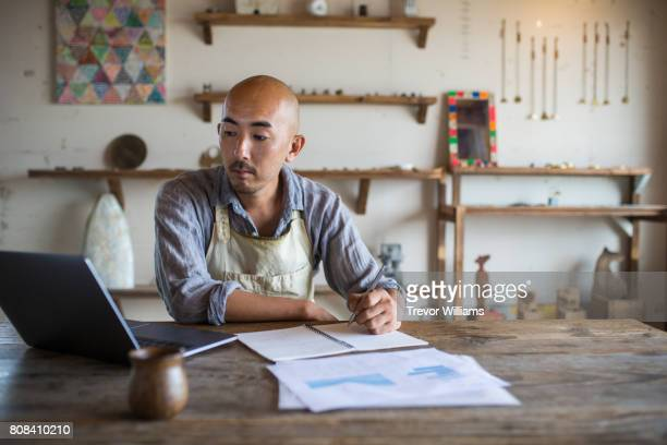 shopkeeper doing his monthly financial planning and bookkeeping - one mature man only stock pictures, royalty-free photos & images