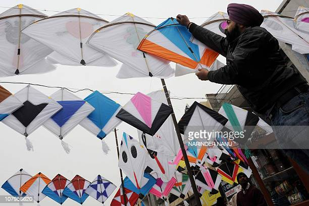 A shopkeeper hangs kites for sale outside his shop in Amritsar on January 12 2010 The demand for kites is rising on the eve of the Lohri Festival an...