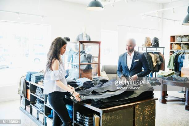 Shopkeeper helping customer choose from a selection of denim in mens clothing boutique