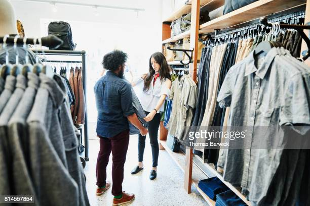 Shopkeeper helping man pick out shirt while shopping in mens boutique