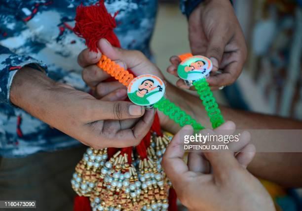 A shopkeeper holds 'rakhis' depicting Indian Air Force Wing Commander Abhinandan Varthaman at a wholesale store ahead of the Hindu festival Raksha...