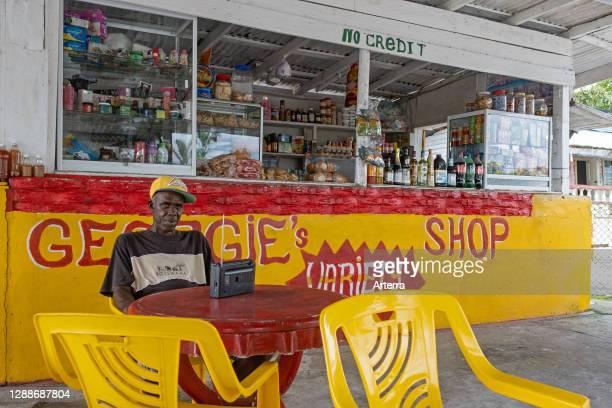Shopkeeper in front of little grocery shop, Essequibo Islands-West Demerara Region, Guyana, South America.