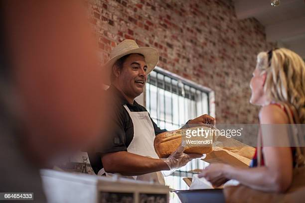 Shopkeeper in shop helping client, white bread