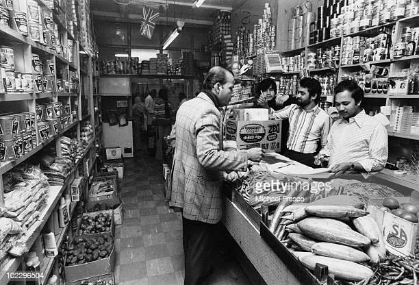 Shopkeeper Komor Uddin serves a customer at his grocer's shop the Taj Stores in Brick Lane east London 5th June 1978
