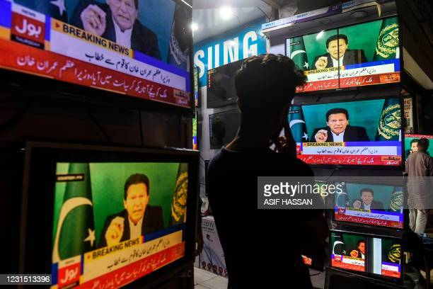 Shopkeeper listens to Pakistan's Prime Minister Imran Khan addressing the nation on television, in Karachi on March 4 after Foreign Minister Shah...