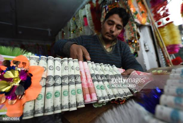 A shopkeeper makes garlands with US dollars and local currency notes at a flower market in Peshawar on December 11 2017 Currency garland is very...