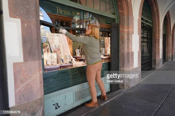 A shopkeeper open a shutter to a window display prior to opening her antiques silver and jewellery store for the first time since March on the first...