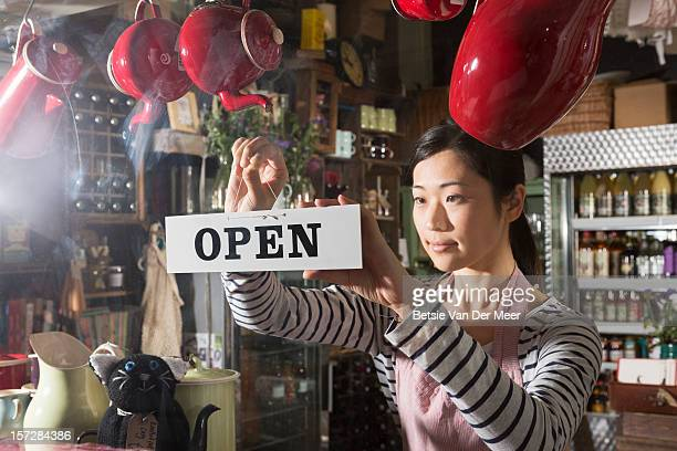 Shopkeeper opens shop by turning open sign.