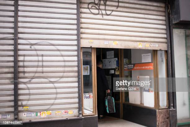 A shopkeeper opens the shutter of the Fed Ex store in Via Milano on November 24 2020 in Turin Italy While the whole country is in various degress of...