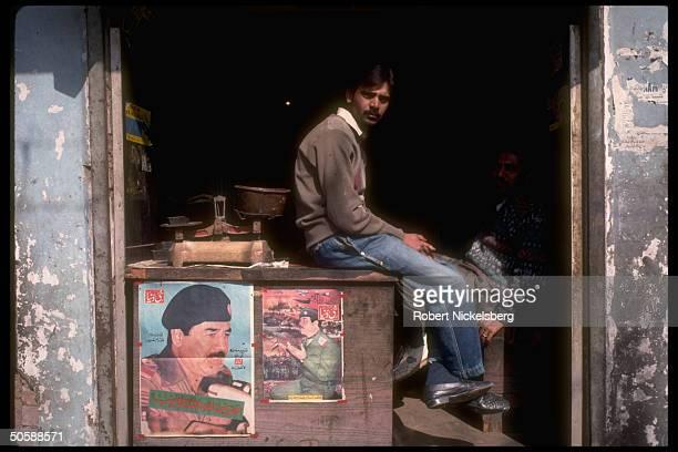 Shopkeeper perching on Saddam Hussein portrait adorned counter reflecting proIraqi gulf war sentiment in Moslem community of Aligarh Uttar Pradesh...