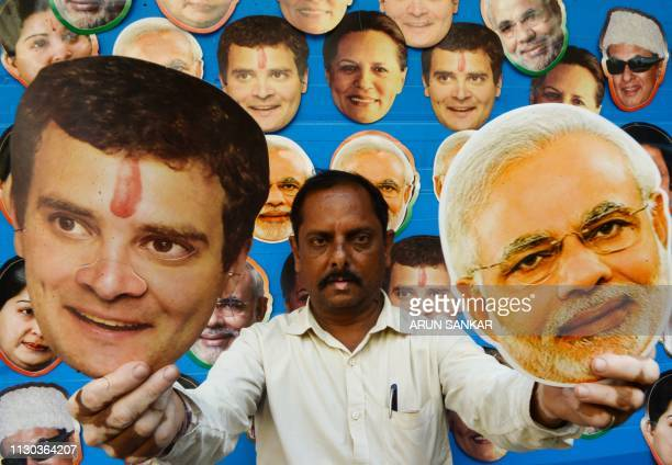 A shopkeeper poses as he holds masks of Indian Congress Party President Rahul Gandhi and Indian Prime Minister Narendra Modi displayed for sale at a...