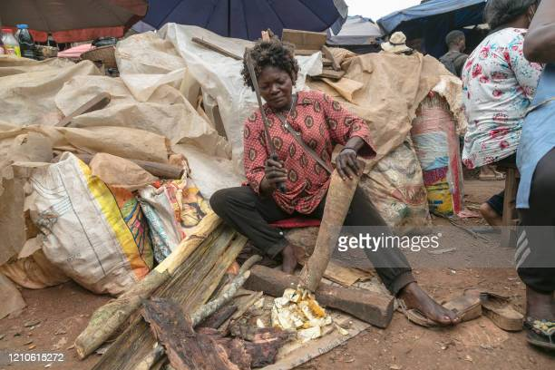 Shopkeeper prepares a traditional recipe for a client by cutting fruits and tree bark at the Mvog Mbi market in Yaounde April 21, 2020. - With a...