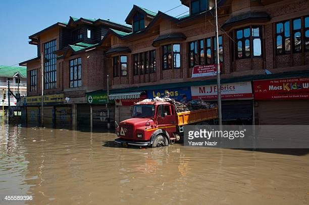 Shopkeeper removes silt from his fabric shop at the flooded city center on September 17 2014 in Srinagar the summer capital of Indian administered...
