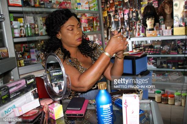 Shopkeeper Ruth Dossouvi applies a skinlightening cream at her shop in Lome on June 29 2018 Africa is experiencing a massive trend of skin bleaching...