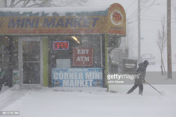 A shopkeeper shovels snow on January 4 2018 in New Haven Connecticut The 'bomb cyclone' was expected to dump heavy snows in New England as the storm...