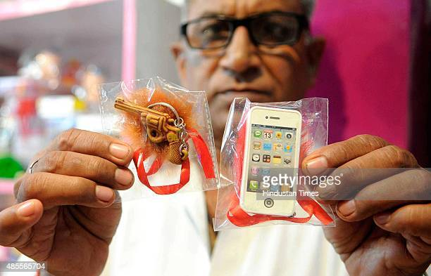 A shopkeeper shows rakhi designed as pistol and mobile phones as the latest trends on the eve of Raksha Bandhan on August 28 2015 in Jaipur India...