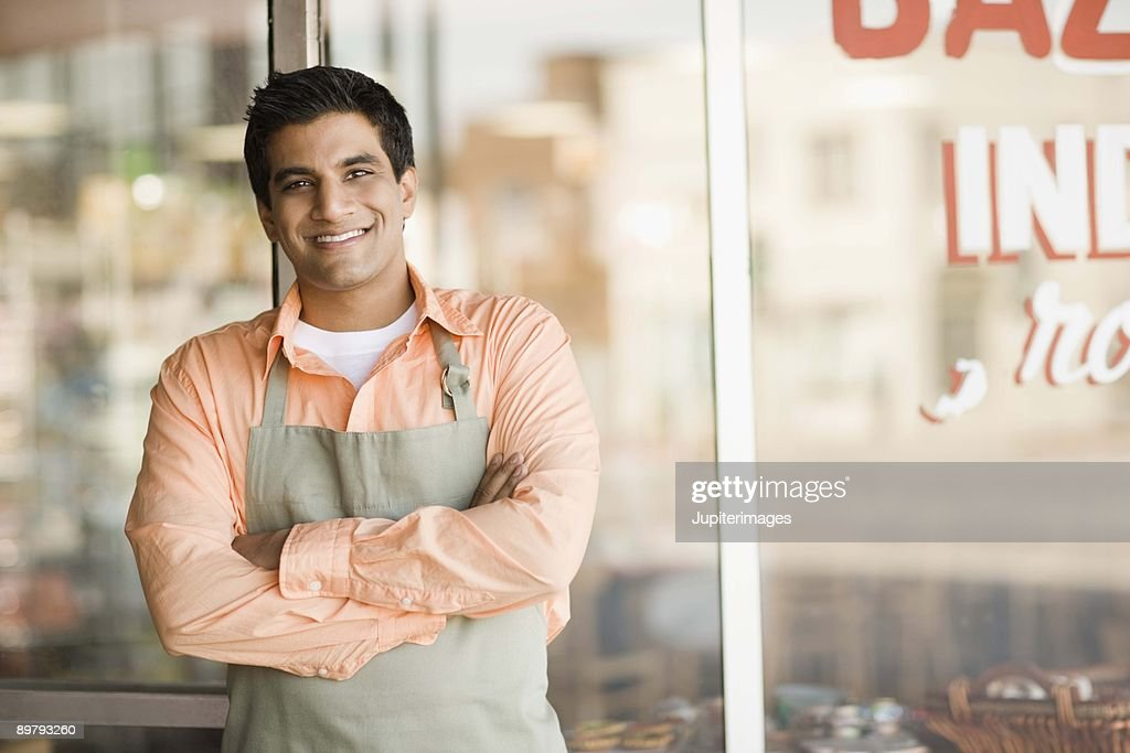 Shopkeeper smiling by storefront : Stock Photo