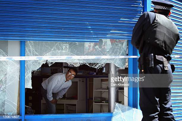 A shopkeeper speaks to a police officer in Brixton after looting on August 8 2011 in London England Pockets of rioting and looting took place across...
