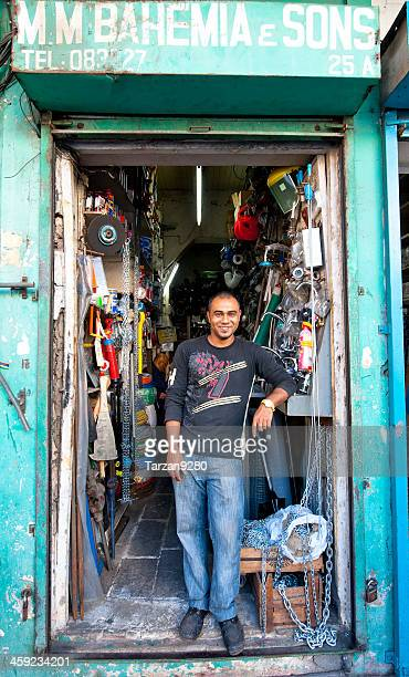 shopkeeper standing in front of his shop - port louis stock photos and pictures