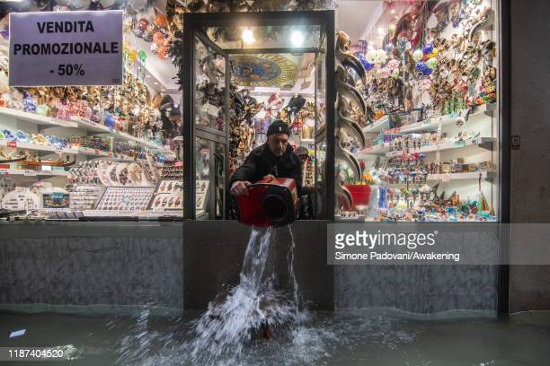 A shopkeeper throws out water from his shop during an exceptional high tide on November 13 2019 in Venice Italy Venice second highest tide after 1966...