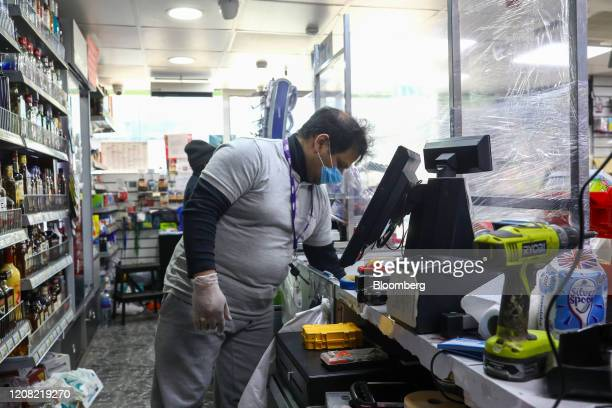 Shopkeeper, wearing a protective face mask and disposable gloves, stands behind a protective screen made of cling film at his shop counter during the...