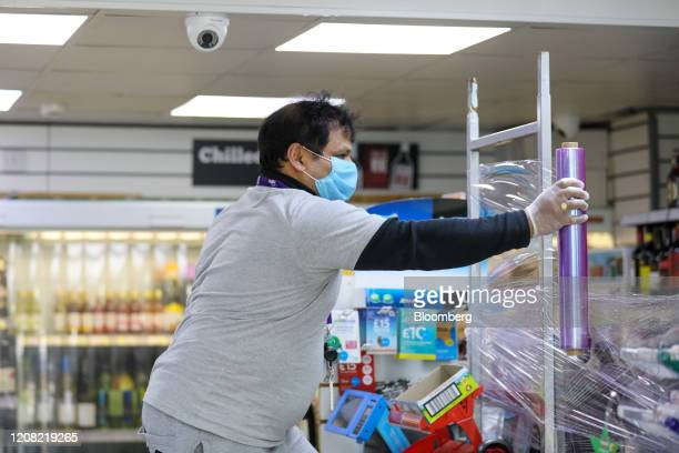 Shopkeeper, wearing a protective face mask, erects a protective screen of cling film at his shop counter during the coronavirus lockdown in London,...