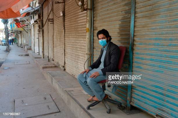 Shopkeeper wearing facemask sits in front of closed shops of a market area in Rawalpindi on March 22 after Punjab Province government announced the...