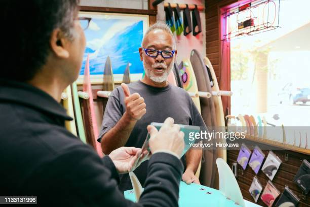 shopkeeper who presents the amount of surfboards to customers in shop - happy merchant stock pictures, royalty-free photos & images