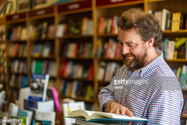 shopkeeper working in a traditional english bookshop - book store stock photos and pictures