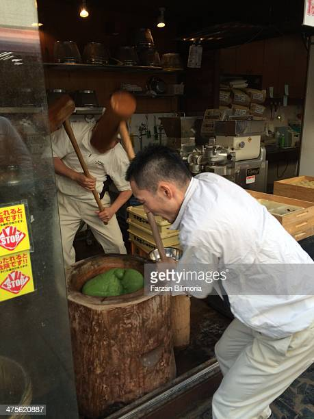 Shopkeepers beating mochi ball mix into shape in Nara