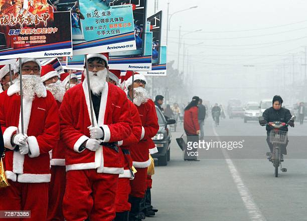 Shopkeepers dressed like Santa Claus hold ad posters as they walk on the street on December 23 2006 in Harbin Heilongjiang Province China While...