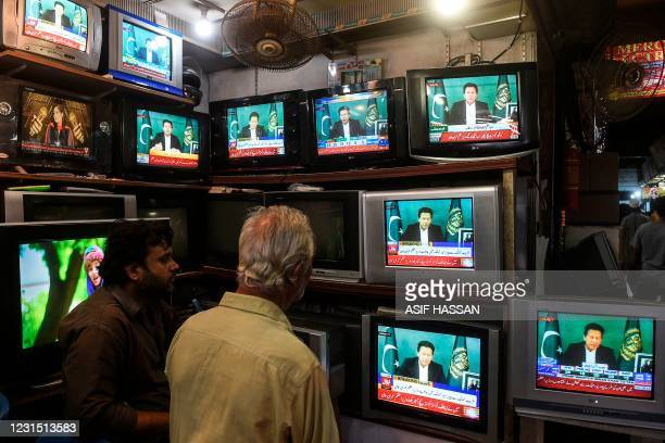 Shopkeepers listen to Pakistan's Prime Minister Imran Khan addressing the nation on television, in Karachi on March 4 after Foreign Minister Shah...