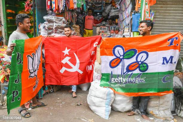 Shopkeepers putting up flags of various political parties to display for sale ahead of assembly elections in Bengal, in Kolkata, India, on February...