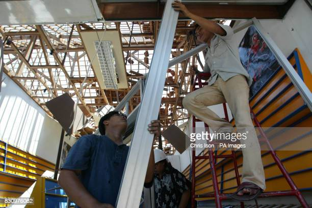 Shopkeepers remove debris as the rebuilding process begins near the Sari Club in Kuta Bali following the car bomb attack at the club in the town *...