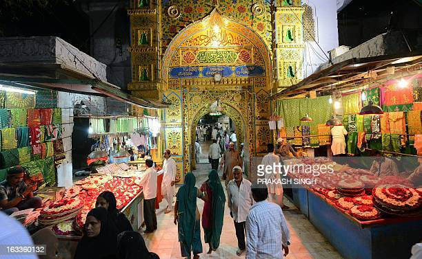 Shopkeepers selling flowers and religious offerings wait for devotees outside the Ajmer Sharif Muslim shrine in Ajmer on March 8 2013 The spiritual...