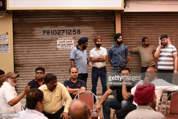Shopkeepers sitting in protest against sealing at Amar Colony Lajpat Nagar after alert about the sealing team will arrive in the market on April 6...