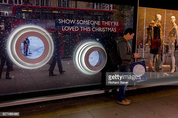 Shopper and the circles of the John Lewis Man in the Moon Christmas theme in the window of the store's Oxford Street branch The story is of a young...