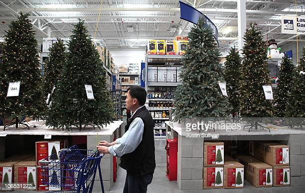 A shopper at a Lowe's home improvement store walks by a display of artificial Christmas trees on November 4 2010 in San Francisco California With...