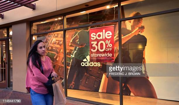 A shopper at an outlet mall walks past an Adidas store on May 21 2019 in Los Angeles More than 170 shoe companies and retailers including Adidas Nike...