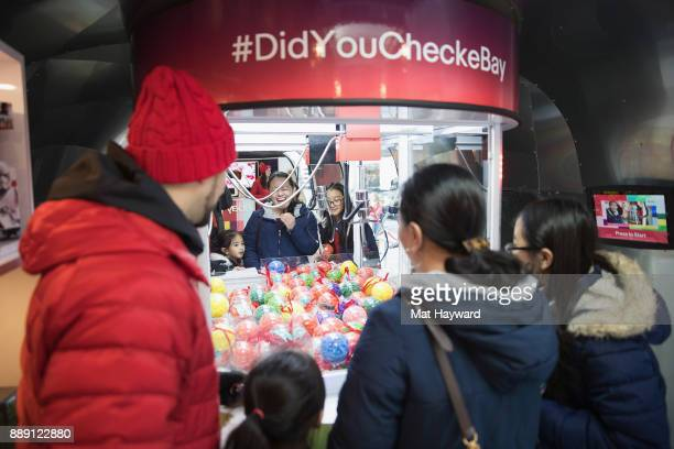 A shopper attempts to win a prize in the eBay Claw Machine during the 'Did You Check eBay' Holiday Airstream tour at Westlake Center Plaza on...