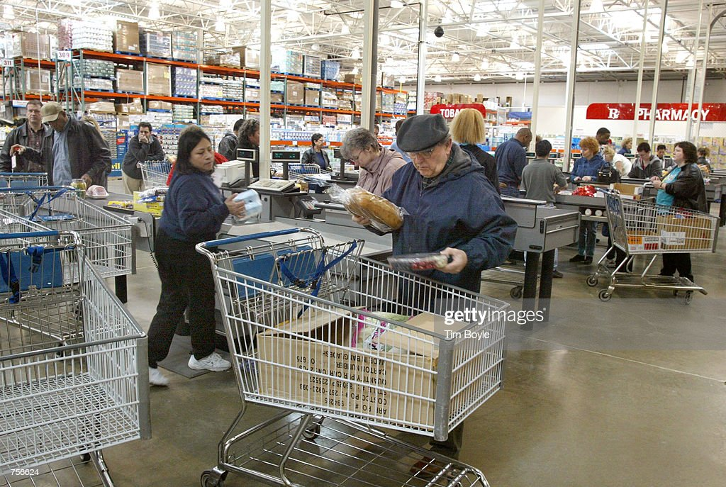 A shopper boxes his purchases after checking out at a Costco