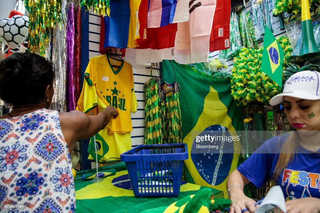 A shopper browses Brazilian themed shirts ahead of the FIFA World Cup games in downtown Sao Paulo, Brazil, on Wednesday, June 13, 2018. In a curious quirk of Brazil's electoral calendar, for the last 28 years Latin America's largest economy has gone to the polls shortly after the World Cup. In the football-obsessed country, politicians have long attempted to hijack the sport to burnish their image. Photographer: Patricia Monteiro/Bloomberg via Getty Images