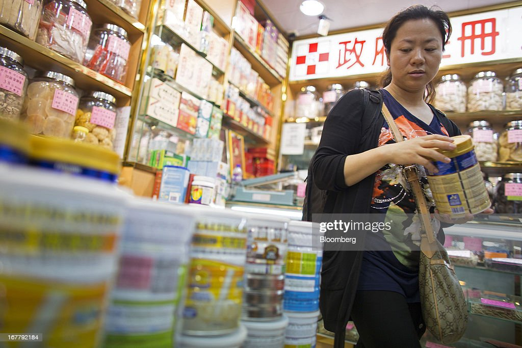 A shopper browses cans of baby formula displayed in a pharmacy in the Mongkok district of Hong Kong, China, on Tuesday, April 30, 2013. Financial Secretary John Tsang on Feb. 27 projected annual growth of 1.5 percent to 3.5 percent this year following 2012's 1.4 percent, the weakest rate since 2009 as Europe's sovereign debt crisis sapped global demand. Photographer: Lam Yik Fei/Bloomberg via Getty Images