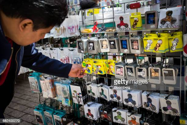 A shopper browses fidget spinners displayed for sale by a street vendor in New York US on Friday May 12 2017 The fidget spinner is a toy that sits...