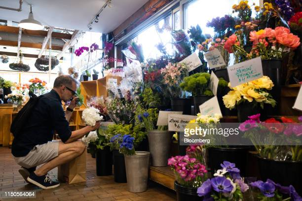 A shopper browses flowers at the Granville Island Public Market in Vancouver British Columbia Canada on Sunday June 2 2019 Statistics Canada is...