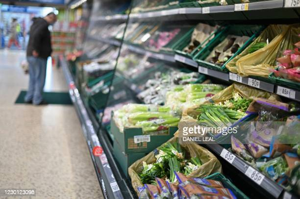 Shopper browses for fruit and vegetables in a Tesco supermarket in London on December 14, 2020. - With just over two weeks to go until Britain leaves...