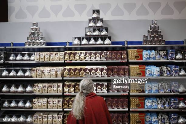 A shopper browses packages of Hershey Co Kisses candies displayed for sale inside of the company's Chocolate World visitor center in Hershey...