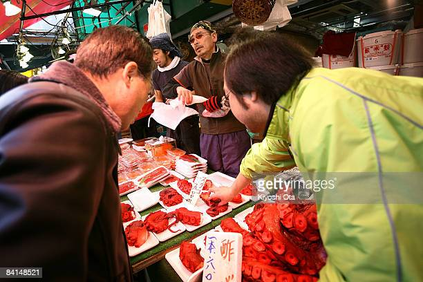 A shopper buys an octopus at a fish stall in the Ameya Yokocho street market on December 31 2008 in Tokyo Japan People shop around in preparation to...