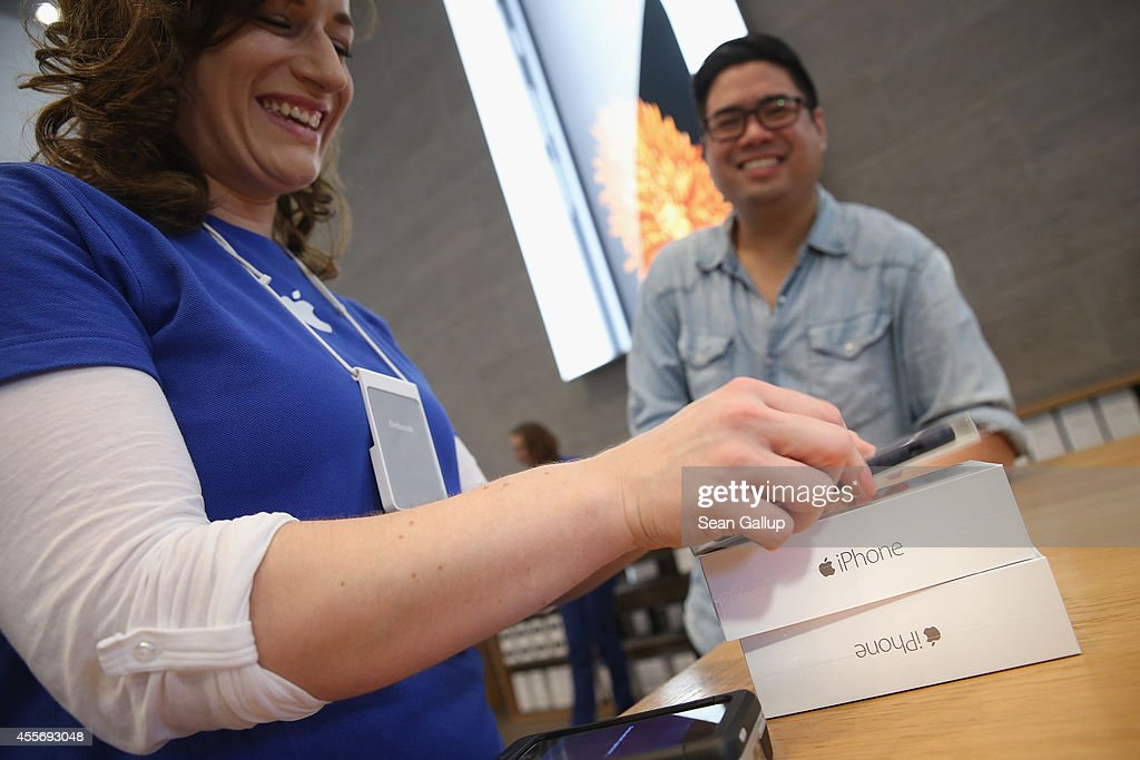 A shopper buys the new Apple iPhone 6 at the Apple Store on the first day of sales of the new phone in Germany on September 19, 2014 in Berlin, Germany. Hundreds of people had waited in a line that went around the block through the night in order to be among the first people to buy the new smartphone, which comes in two versions: the Apple iPhone 6 and the somewhat larger Apple iPhone 6 Plus.